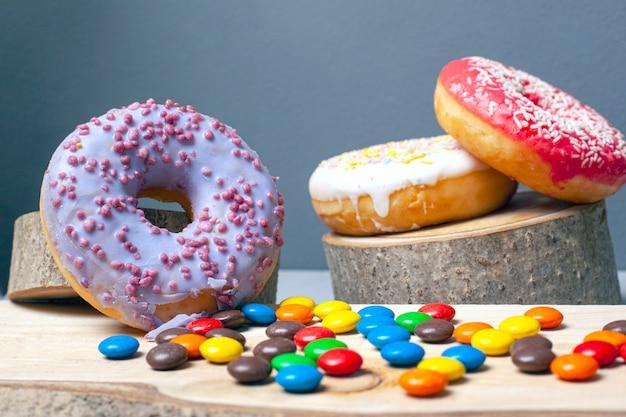 Süße farbige donuts mit zuckerguss und verschiedenen süßigkeiten auf dekorativen holzuntersetzern des waldes auf grauem hintergrund.