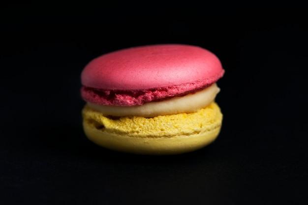 Süße farbige makrone auf schwarzem hintergrund isoliert isolated