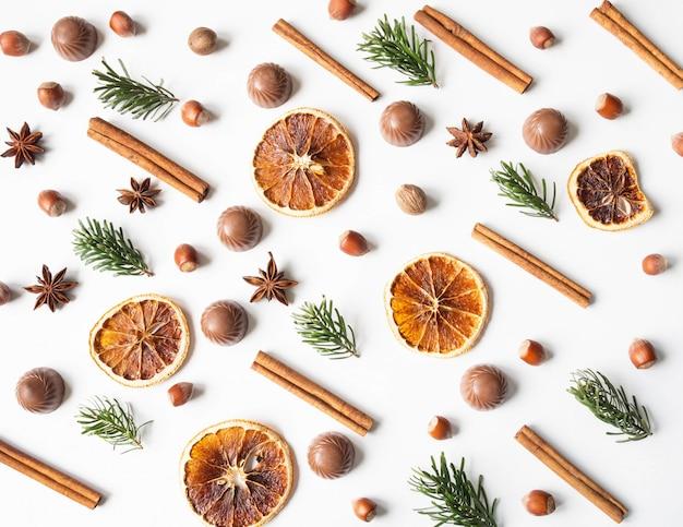 Süße festliche gebäckzusammensetzung mit schokolade, trockenen orange scheiben, tannenbaum, nüssen und gewürzen auf einem weißen hintergrund.