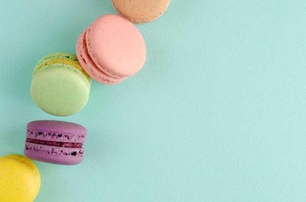 Süße französische nachtische von verschiedenen farbmakronen auf pastellblau