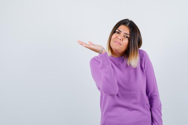 Süße frau, die vorgibt, etwas in einem lila pullover zu halten und selbstbewusst auszusehen, vorderansicht.