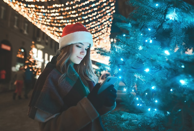 Süße frau in einer weihnachtsmütze steht auf einem baum auf einer straße, die an einem feiertag geschmückt wird und benutzt ein smartphone