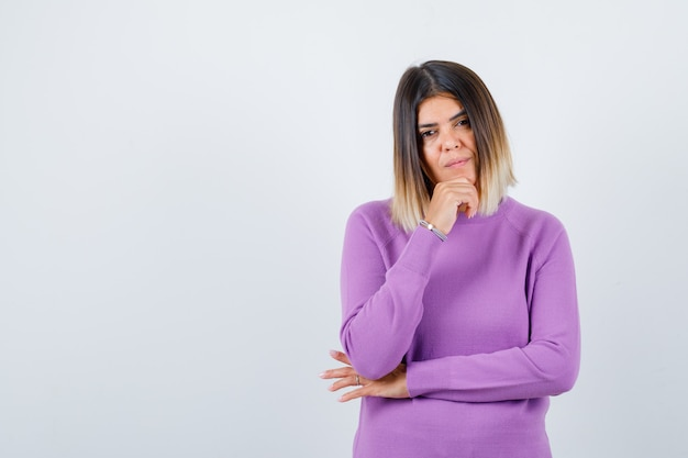 Süße frau in lila pullover mit hand am kinn und nachdenklich aussehend, vorderansicht.