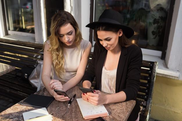 Süße freundinnen benutzen geräte, die auf der sommerveranda im café sitzen