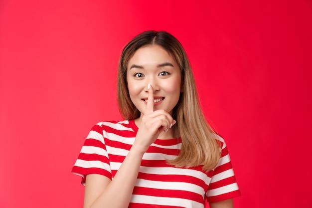 Süße, freundliche, fröhliche asiatische freundin, die geheimes tratschen lächelndes versprechen teilt, geheimes meer nicht zu erzählen ...