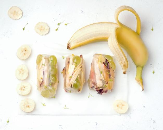 Süße frühlingsrollen mit früchten neben einer frischen banane auf weiß. diätessen