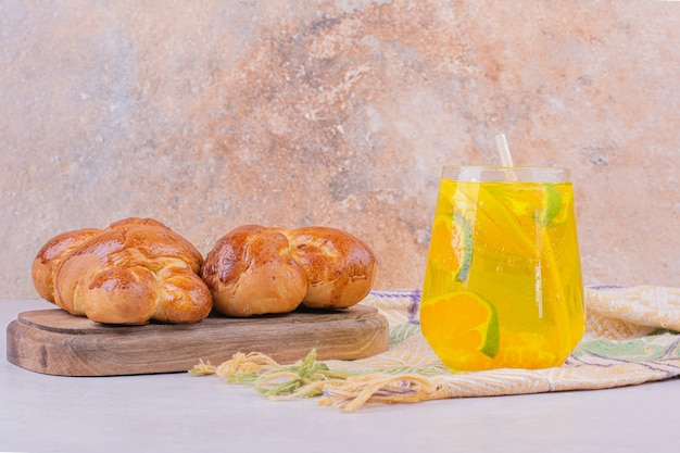 Süße gebäckbrötchen auf holzplatte mit einem glas limonade.