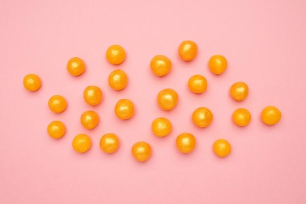 Süße gelbe süßigkeiten auf einem rosa, runden süßen lebensmittel