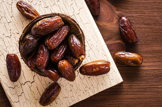 Süße getrocknete datteln tragen in der kleinen hölzernen schüssel auf einem schäbigen brett früchte. ansicht von oben