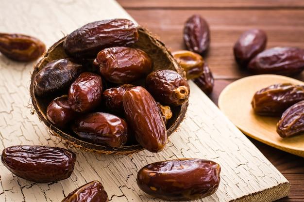 Süße getrocknete datteln tragen in der kleinen hölzernen schüssel auf einem schäbigen brett früchte