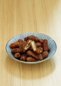Süße getrocknete datteln tragen in einer schüssel und auf dem tisch früchte