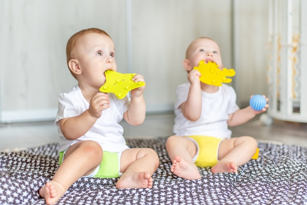 Süße glückliche babys spielen zusammen mit spielzeug auf dem boden und nehmen sie in den mund