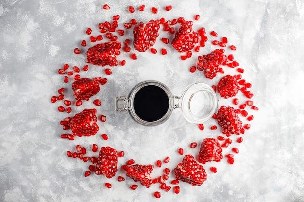 Süße granatapfelsoße oder -sirup für fleisch und fische nannten narsharab, in einem glasgefäß mit gereinigtem granatapfel, selektiver fokus