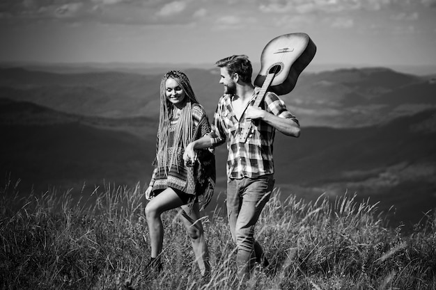 Süße harmonie in den bergen. glückliche paar reisende haben einen spaziergang, lächeln und gitarre spielen