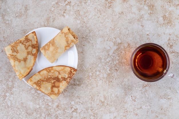 Süße hausgemachte crepes mit einer tasse heißen tees
