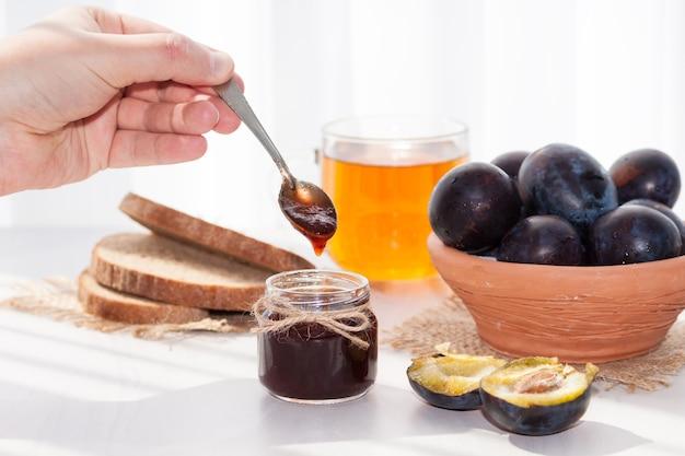 Süße hausgemachte pflaumenmarmelade und früchte auf einem weißen tisch an einem sonnigen tag.
