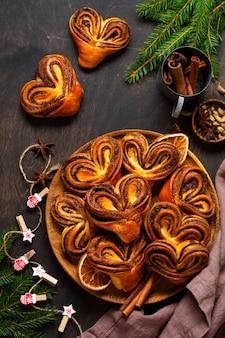 Süße hausgemachte zimtschnecken in herzform auf einem alten retro-stuhl. neujahrsstimmung. traditionelle schwedische zimtschnecken. selektiver fokus