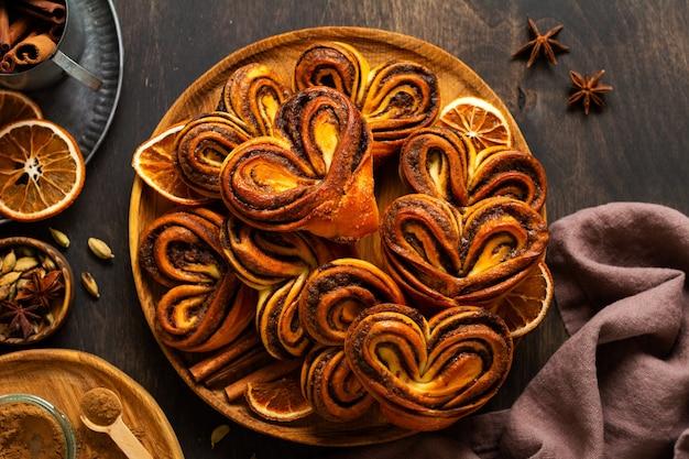 Süße hausgemachte zimtschnecken in herzform im alten retro-stil. neujahrsstimmung. traditionelle schwedische zimtschnecken. selektiver fokus