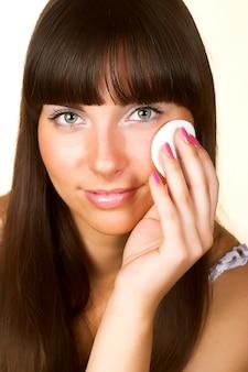 Süße hautpflege. attraktives mädchen, das gesichtsmaske anwendet. isoliert auf weiß