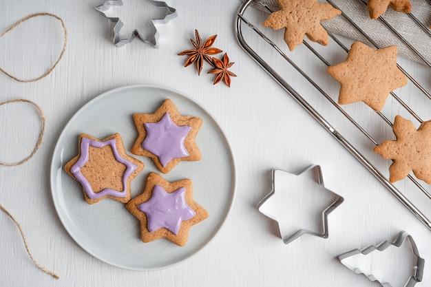 Süße herzhafte lebkuchenplätzchen, die mit violettem zuckerguss auf weißem holztisch mit schneidern verzieren