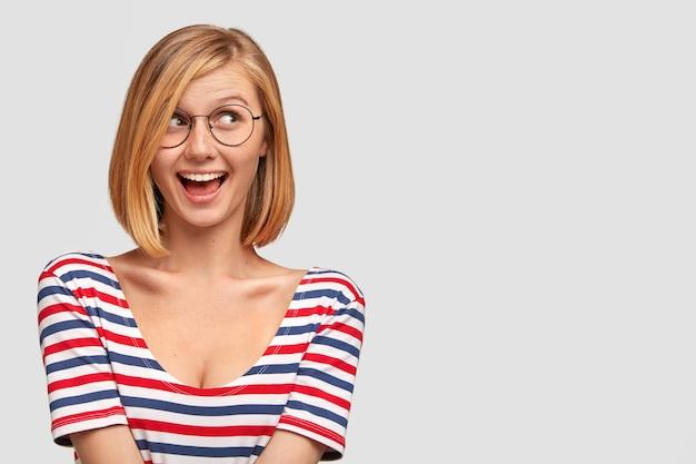 Süße hübsche frau hat positive gefühle, trägt eine brille, ein gestreiftes t-shirt, hat eine frisur und einen freudigen ausdruck