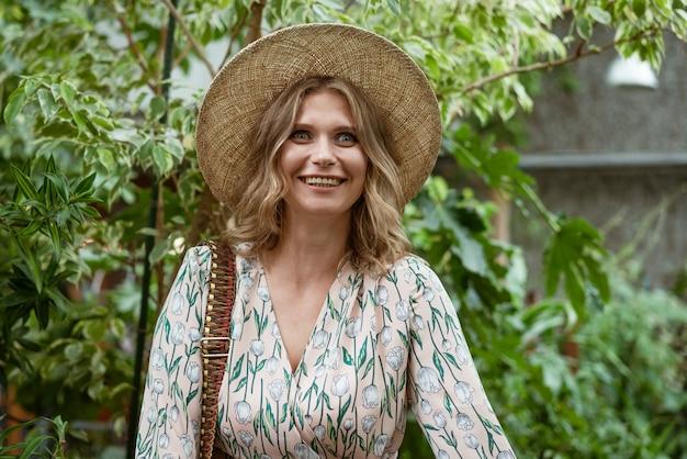 Süße junge blonde frau posiert und lächelt im grünen im gewächshaus