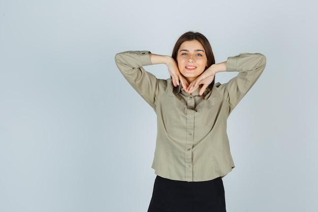 Süße junge frau, die ellbogen ausdehnt, während sie in hemd, rock lächelt und fröhlich aussieht, vorderansicht.