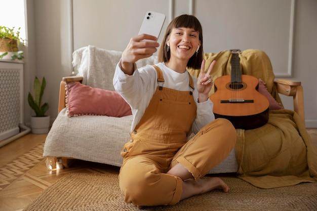 Süße junge frau, die neben ihrer gitarre ein selfie macht