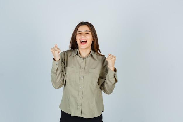 Süße junge frau, die siegergeste zeigt, während sie im hemd schreit und glückselig aussieht, vorderansicht.