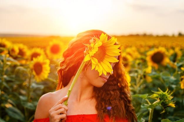 Süße junge frau hält sonnenblume in der hand, während sie bei sonnenuntergang auf dem feld steht schöne sanfte...