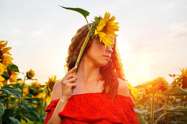 Süße junge frau hält sonnenblume in der hand, während sie bei sonnenuntergang auf dem feld steht