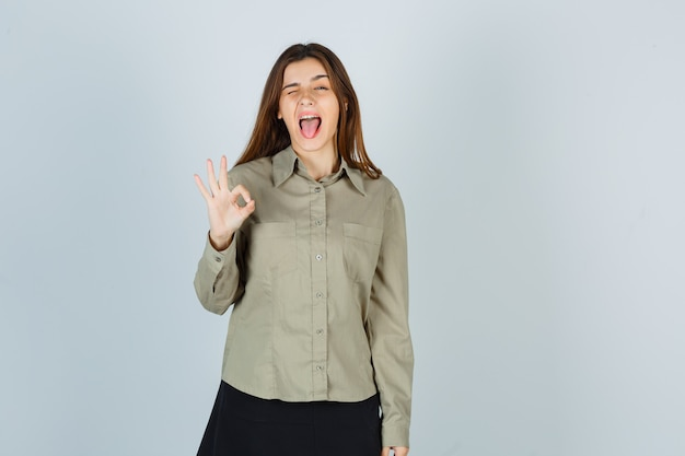 Süße junge frau im hemd, rock, der beim blinzeln eine gute geste zeigt, die zunge herausstreckt und verrückt aussieht, vorderansicht.