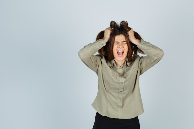 Süße junge frau im hemd, rock, die in die kamera knurrt, während sie mit den händen an den haaren reißt und traurig aussieht, vorderansicht.