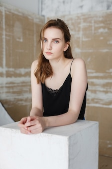 Süße junge hübsche frau mit langen haaren posiert auf abstraktem hintergrund im studio