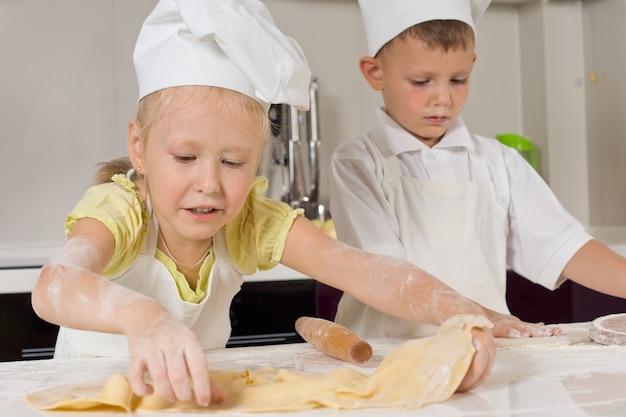Süße junge köche sind damit beschäftigt, essen in der küche zuzubereiten.