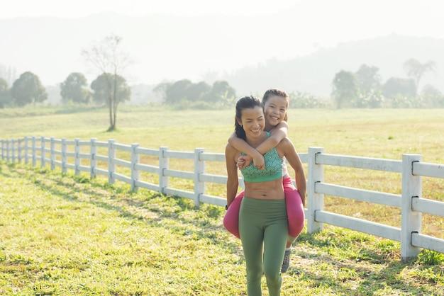 Süße junge tochter auf einer huckepack-fahrt mit mutter, die ihre zeit auf dem land verbringt. glückliche familie auf der wiese im sommer in der natur. outdoor-sport und fitness, bewegungslernen für die entwicklung von kindern.