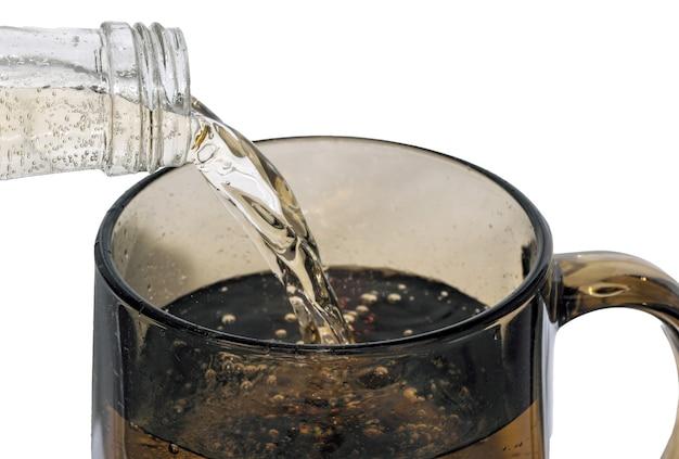 Süße kalte limonade wird aus einer flasche in ein dunkles glas auf weißem hintergrund gegossen