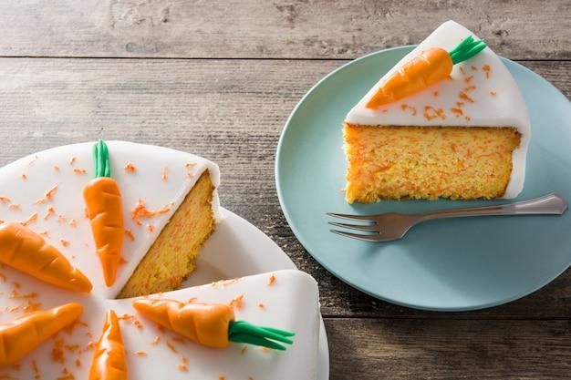 Süße karottenkuchenscheibe auf holztisch