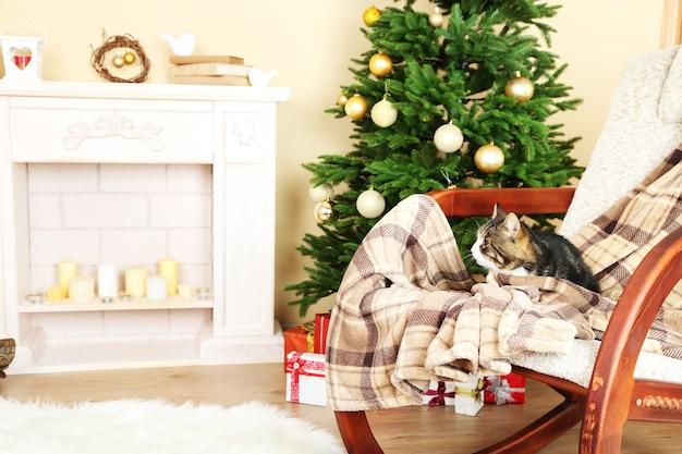 Süße katze auf schaukelstuhl vor dem kamin