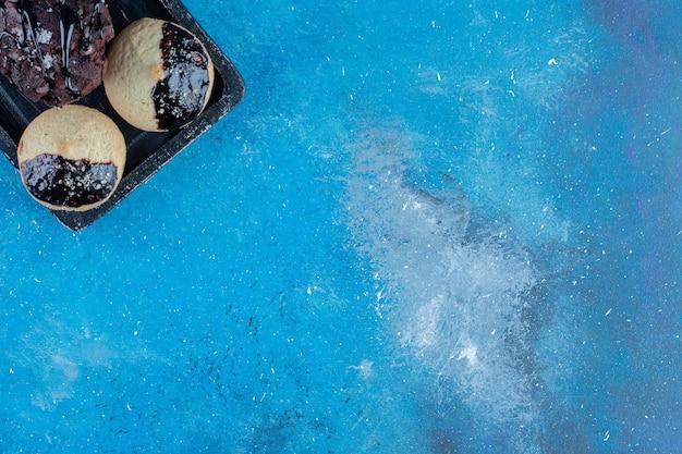 Süße kekse auf dem brett, auf dem blauen hintergrund. hochwertiges foto