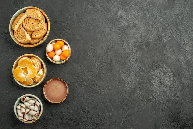 Süße kekse der draufsicht mit bonbons auf dunklem hintergrund