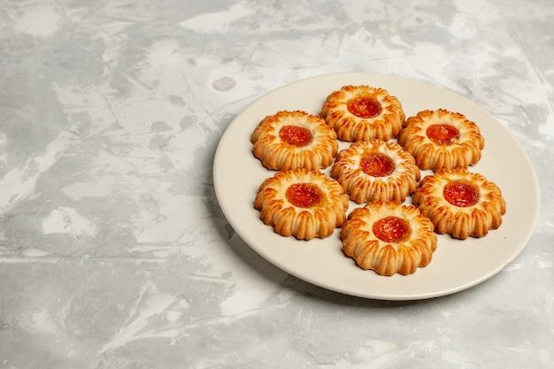 Süße kekse der vorderansicht mit orangenmarmelade auf dem süßen keks der weißen oberfläche des kekszuckerkuchens