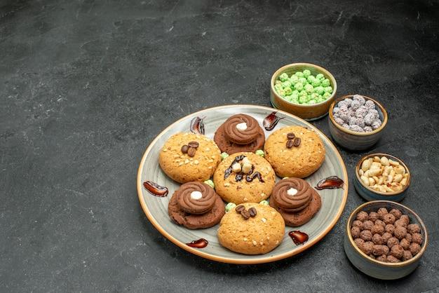 Süße kekse der vorderansicht mit süßigkeiten auf grauzone