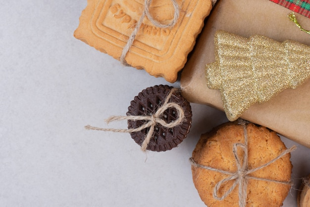 Süße kekse im seil mit geschenk und goldenem weihnachtsspielzeug auf weißer oberfläche
