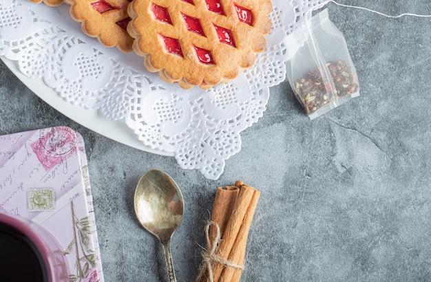 Süße kekse mit löffel und zimtstangen.