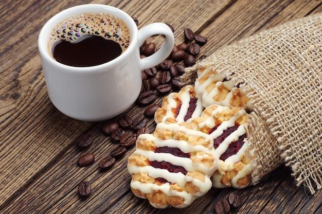 Süße kekse mit marmelade und zuckerguss und tasse kaffee auf vintage-holztisch