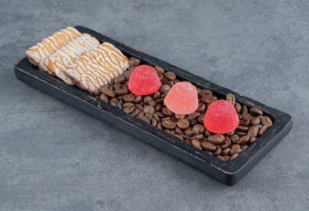 Süße kekse mit roten geleesüßigkeiten und kaffeebohnen