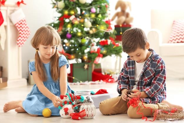 Süße kinder, die weihnachtshandwerk auf dem boden machen