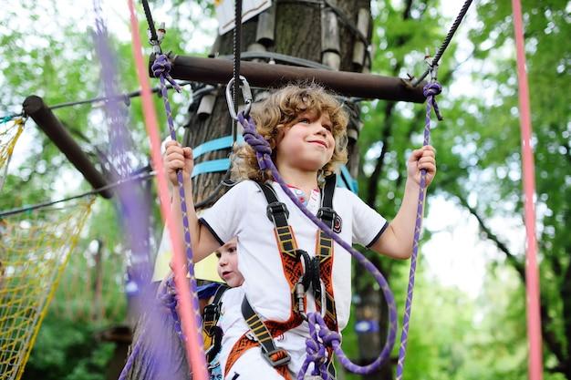 Süße kinder - ein junge im abenteuerpark klettert oder passiert hindernisse auf der seilstraße.