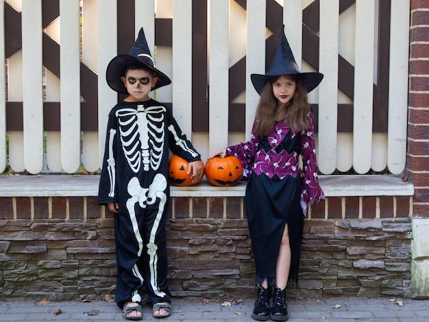 Süße kinder, ein junge in einem skelettkostüm und ein mädchen in einem hexenkostüm feiern halloween